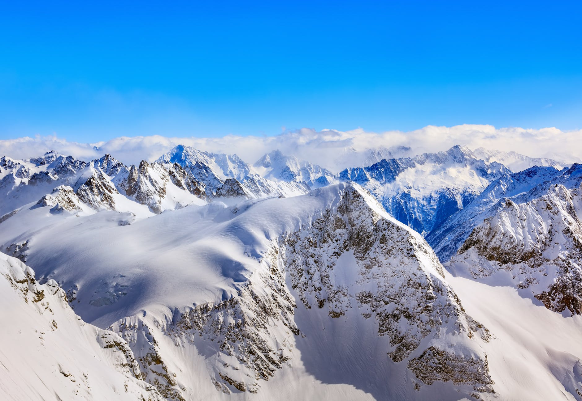 areal photography of snow coated mountains under clear blue sky